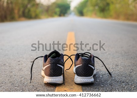 Close up new black running shoes on asphalt road in morning time - stock photo