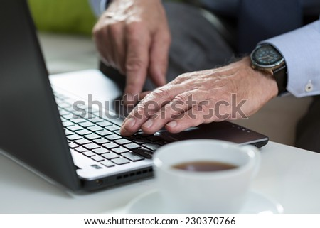Close-up od older man using the  laptop in his office - stock photo