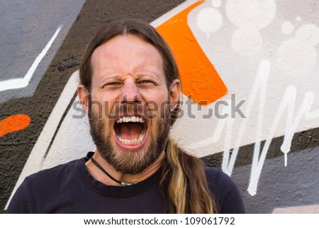 Close-up of a angry, screaming man against a graffiti wall. - stock photo