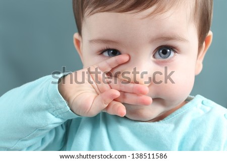 Close up of a baby girl looking at camera with a big blue eyes with a green unfocused background - stock photo