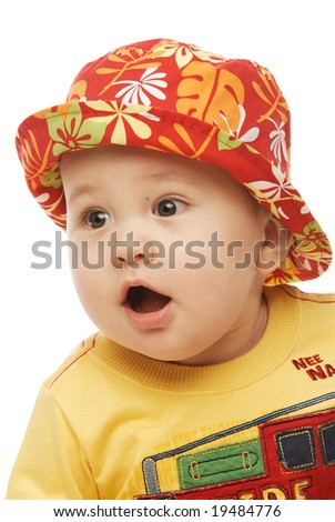 Close up of a baby in red panama looking sideways surprised his mouth open