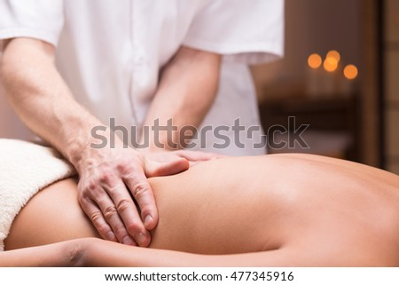 Close-up of a back massage performed on a dark-skinned person