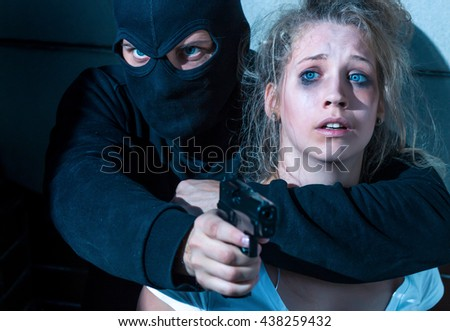 Close-up of a balaclava-clad bandit holding a young terrified woman and pointing his gun at somebody - stock photo