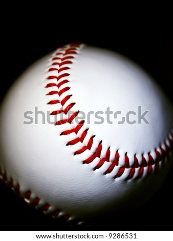 close-up of a baseball against dark background horizontal - stock photo