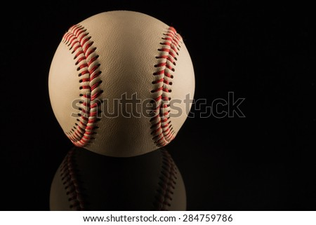 Close up of a baseball ball on black background with reflection - stock photo