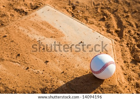 Close up of a baseball home plate with a baseball sitting on the lower right hand corner.