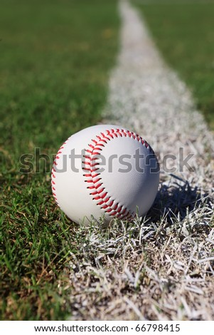 Close-up of a baseball on the outfield foul line. - stock photo