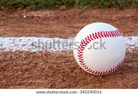 Close-up of a baseball sitting near the foul line - stock photo