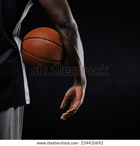 Close-up of a basketball in hand of a young african athlete against black background with copyspace - stock photo