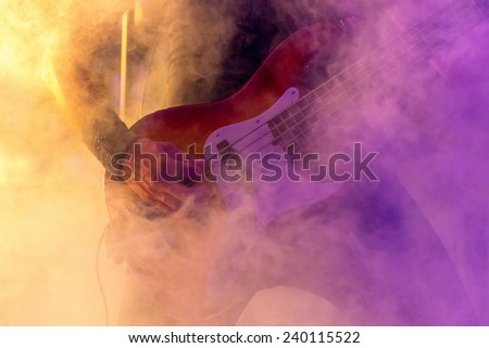 Close up of a bass guitar's hand while the player performs live on the stage during a concert, surrounded by colored artificial smoke effects. - stock photo