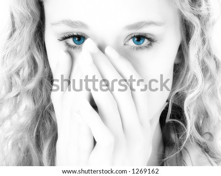 Close-up of a beautiful blonde woman covering her mouth with her hands. Black and white with blue eyes. - stock photo