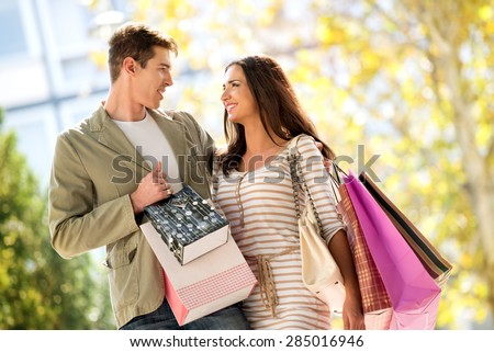 Close-up of a beautiful couple in love walking happily through town after shopping, hugging and carrying shopping bags in their hands. - stock photo