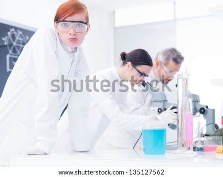 close-up of a beautiful girl student in a chemistry lab looking confused  in the cameraand another two scientists analyzing under microscope - stock photo