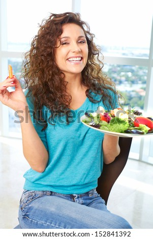 Close-up of a beautiful happy female eating a salad
