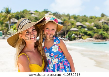 Close up of a beautiful mom woman in yellow dress and beach straw hat with her pretty blonde little daughter at tropic seaside. Both smile to camera. Happy family on the beach. Happy mothers day. - stock photo