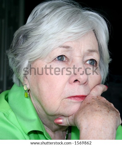 Close-up of a Beautiful Pensive Older Woman Isolated On a Black Background - stock photo