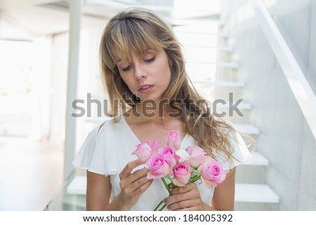 Close-up of a beautiful sad young woman with flowers standing on stairs at home