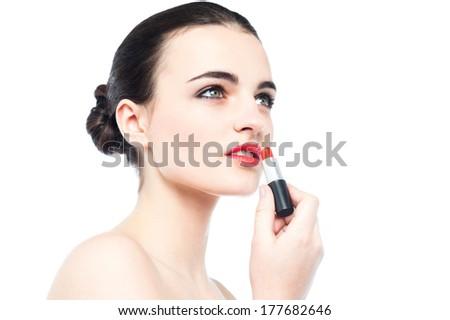 Close up of a beautiful woman applying a lipstick - stock photo