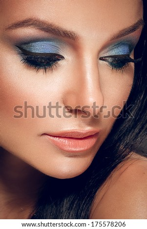 Close up of a beautiful woman with bright blue make up - stock photo