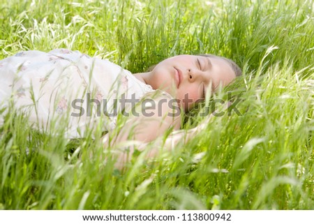 Close up of a beautiful young blond girl sleeping on long green grass in a garden. - stock photo