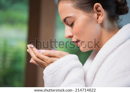 Close up of a beautiful young woman smelling flowers in spa - stock photo