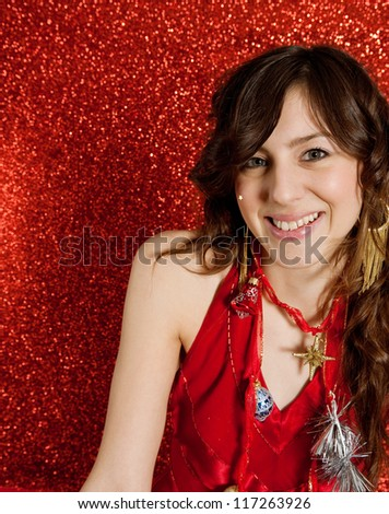 Close up of a beautiful young woman wearing Christmas tree decorations as a necklace while standing against a red glitter background, smiling.