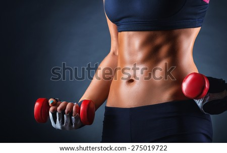 Close-up of a belly muscles sports woman with dumbbells on a dark background - stock photo
