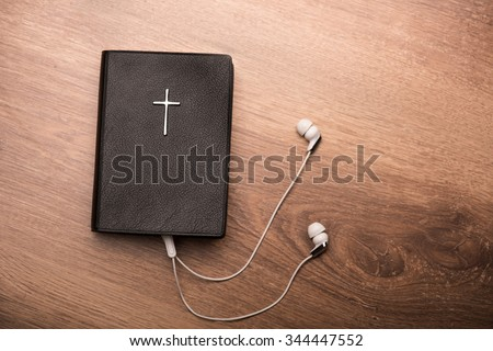 Close up of a Bible connected with earphones - stock photo