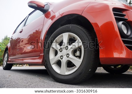 Close up of a black car tyre park on the road. Red Car. - stock photo