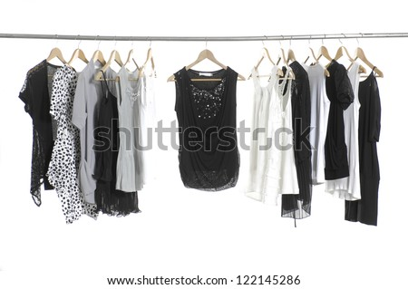 close up of a black dress and Fashion female clothing hanging on hangers - stock photo