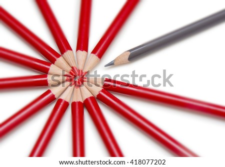 Close up of a black pencil standing out from a circle formed by the tips of several red pencils. Isolated on white