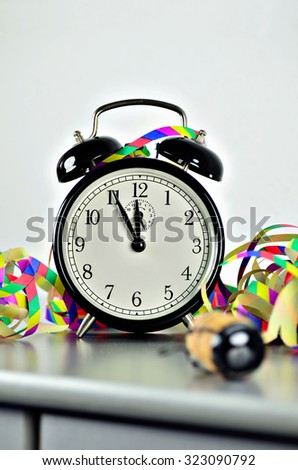 close up of  a black retro alarm clock, around midnight, with paper streamers and cork from a bottle of sparkling wine, vertical / New Year´s Eve
