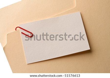 Close up of a blank note clipped on a file folder. - stock photo