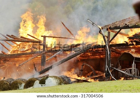 Close up of a blazing fire burns through the roof rafters of an old farm home on a mountain resort - stock photo