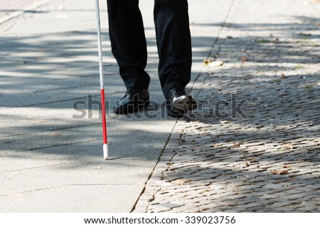 Close-up Of A Blind Man Standing With White Stick On Street - stock photo