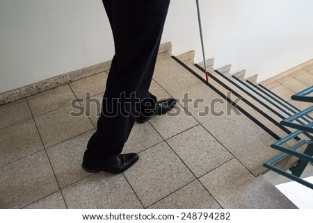 Close-up Of A Blind Man Walking Near Stairway Holding Stick - stock photo