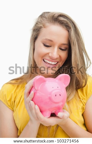 Close-up of a blond woman looking a piggy-bank against white background