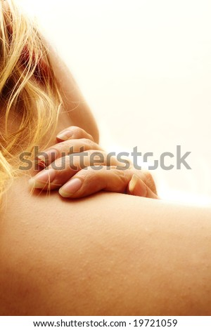 close up of a blond woman massaging her neck