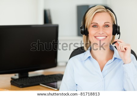 Close up of a blonde smiling woman wearing headset looking into camera in her office - stock photo