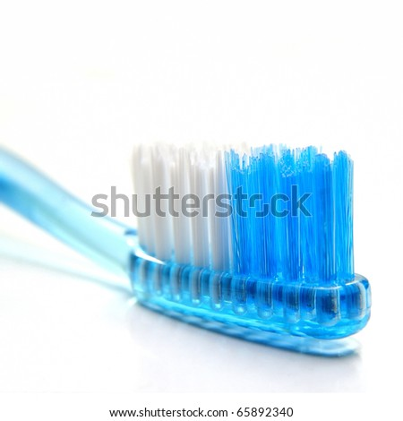 Close up of a blue toothbrush over white background - stock photo