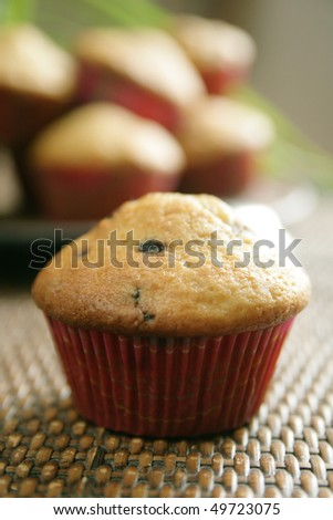 Close up of a blueberry  and oat muffin with basket full of muffin in background