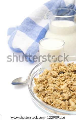 Close-up of a bowl of cereal with a jug of fresh milk, isolated on the white background. - stock photo