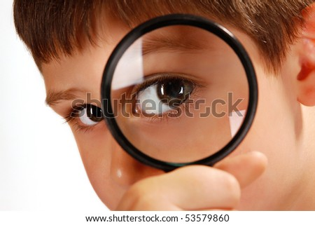 close up of a boy looking through magnifying glass - stock photo