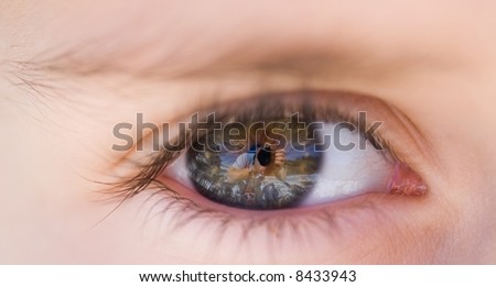 Close-up of a boy's eye reflecting the photographer and the landscape