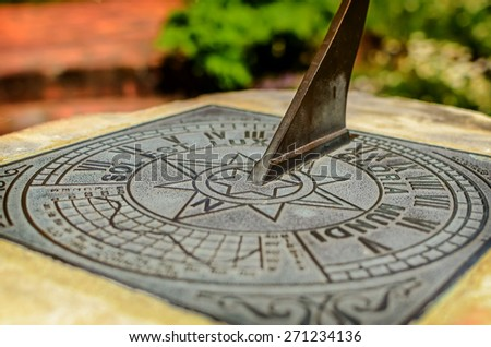 Close-up of a brass sundial mounted on a stone plinth in Wellington Botanic Garden, New Zealand. Soft selective focus and shallow depth of field - stock photo