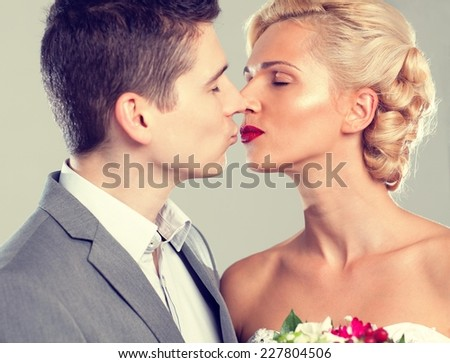 Close up of a bride and groom kissing.