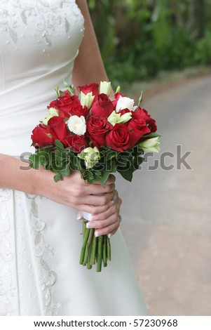 Close-up of a bride holding a beautiful bouquet. - stock photo