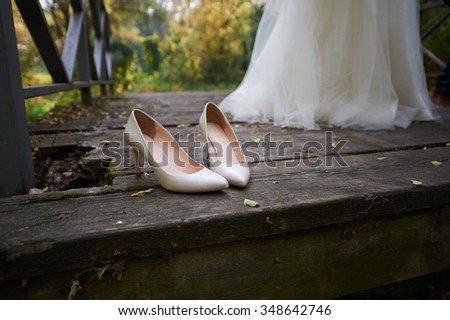 close-up of a bride's shoes on a wooden floor. In the background, a fragment of the bride dress. Bride standing bare feet on the wooden floor. photo taken outside