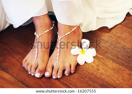Close-up of a bride wearing bead sandals on her feet. - stock photo