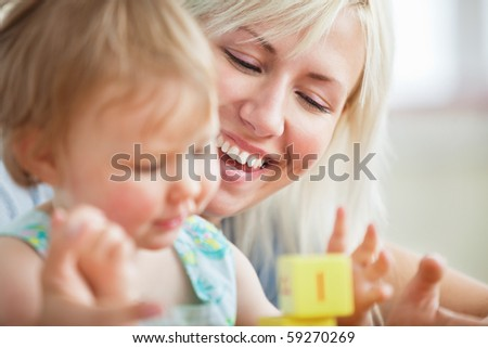 Close-up of a bright mother playing with her daughter at home